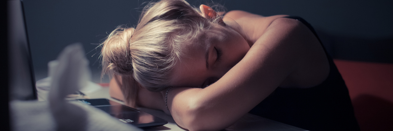 A woman resting her head on her desk.