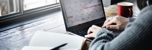 woman sitting at a cafe typing on a calendar on her computer next to an open journal