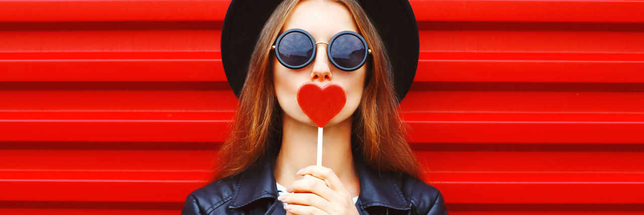 Fashion pretty young woman with red lollipop heart wearing black hat leather jacket over urban background
