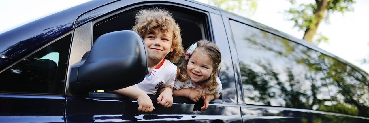 Children look out from a car window.