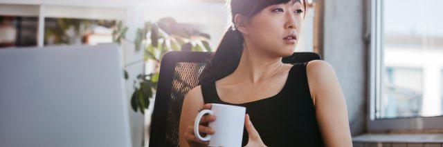 business woman sitting at desk taking coffee break