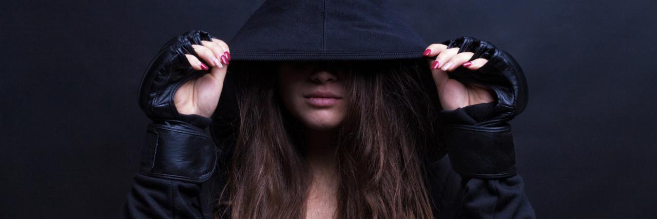 A woman wearing a black hoodie.