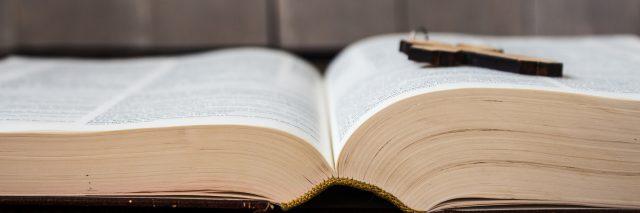 wooden cross lying on an open bible