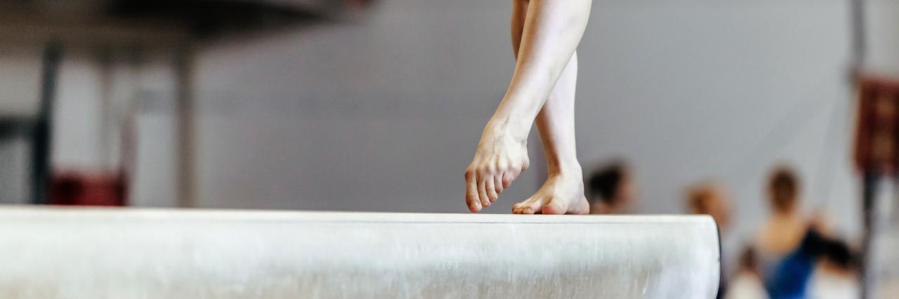 Woman gymnast exercises on balance beam.