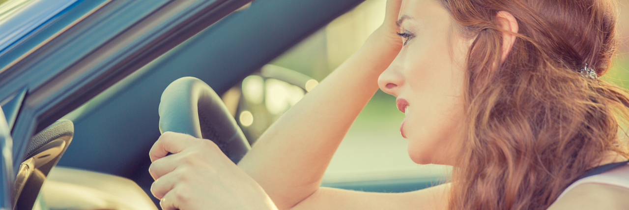 side view of stressed panicked woman driving car