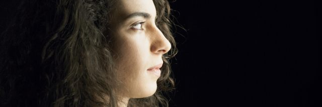 profile of a woman with dark curly hair looking to the right