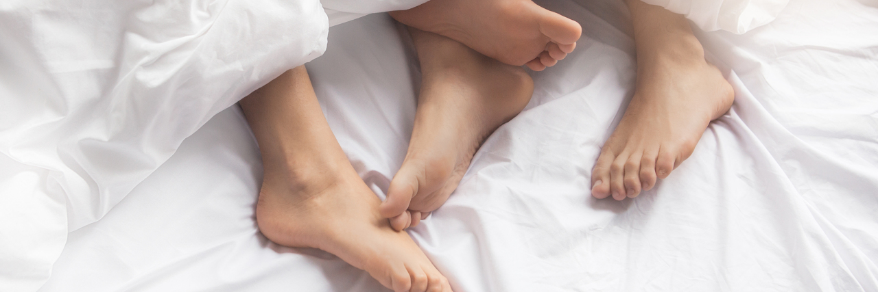 Couple's feet sticking out from under covers.