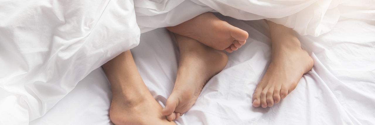 a couple's feet sticking out from under the sheets