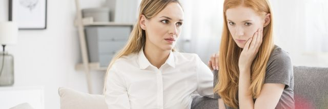 two women sitting on sofa comforting during panic attack