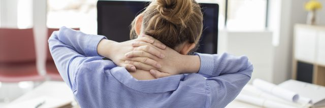 woman in office tired or stressed with hands behind neck