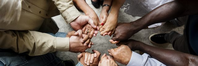 Group of diverse hands holding each other support together