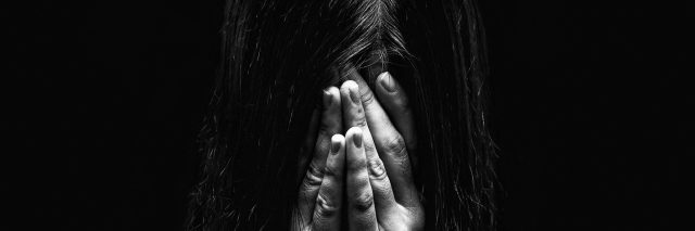 black and white photo of woman covering face with hands