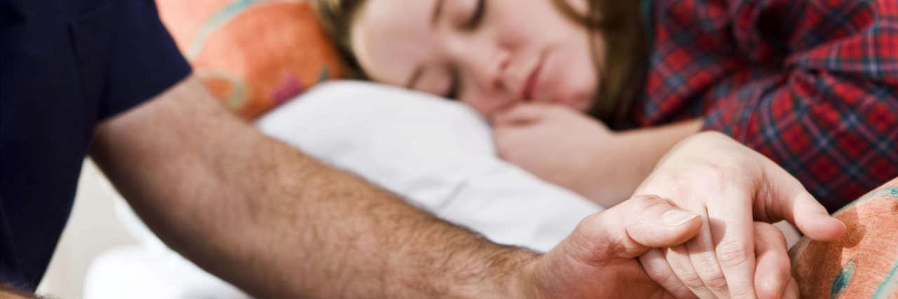 A man holding a girl's hand, who is laying in bed.