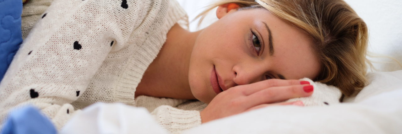 worried woman lying on bed thinking