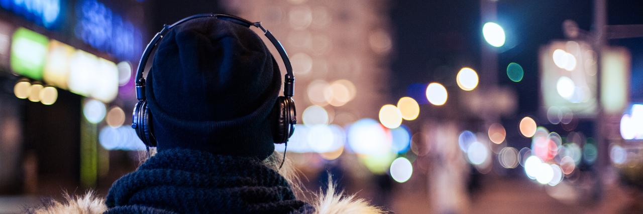 Woman wearing headphones walking at night.