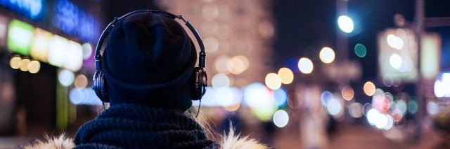Woman wearing headphones walking at night.