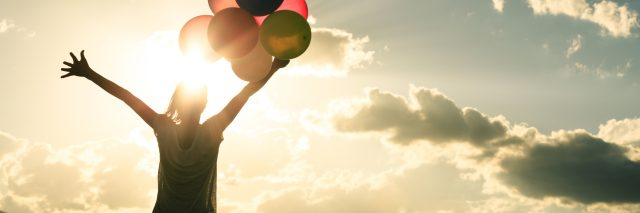 woman in grassland with colourful balloons against sun