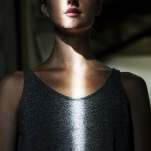 A woman in the dark, with a line of light shining on her.