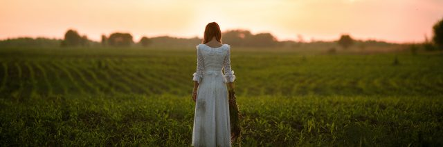 Young woman in long white lace dress on cornfield at sunset. Back view.