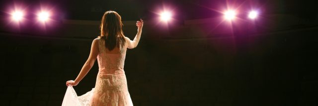 A woman in a gown on a stage with stage lights focusing on her.