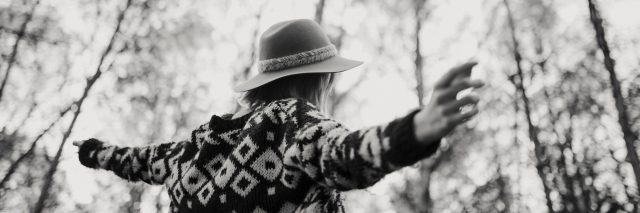 black and white photo of a woman wearing a sweater and a hat while walking in the forest