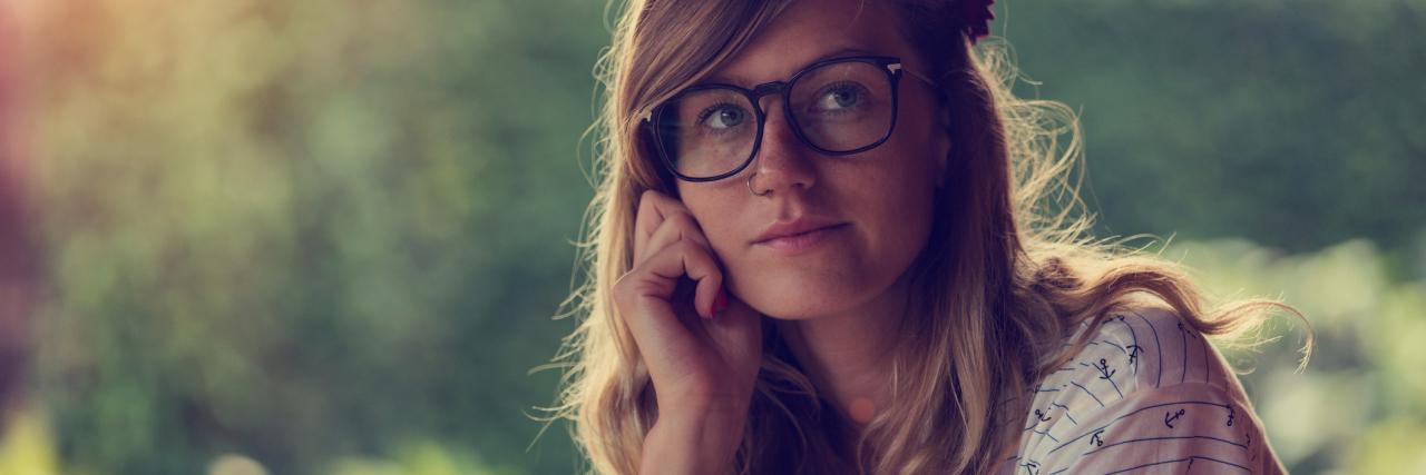 young woman in garden contemplative