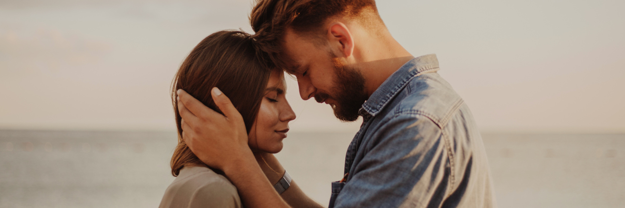 man and woman standing in front of the ocean and touching foreheads