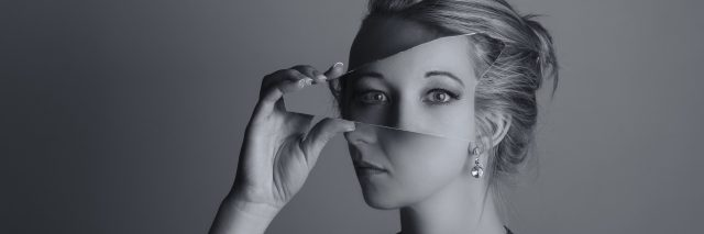 A picture of a woman holding a mirror to her face, showing her eyes at a unique angle.