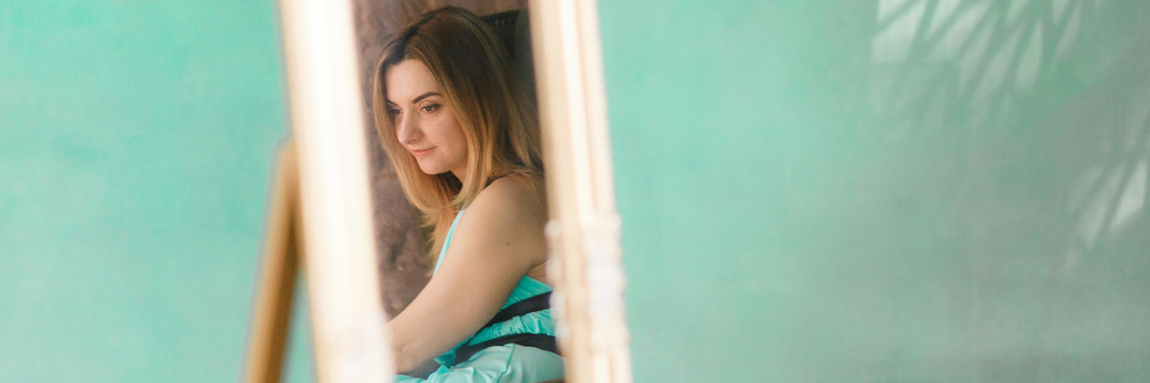 selective focus of woman's reflection in mirror against green wall