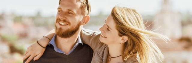 man and woman smiling outside in a city