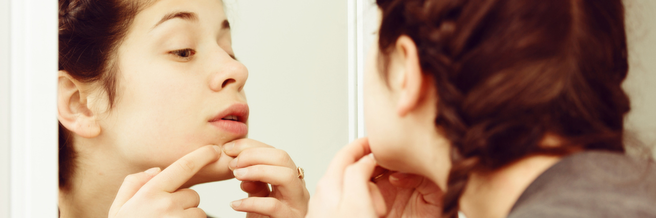 young woman cleaning pores or picking skin in front of mirror