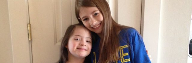 """Two sisters hugging. One with Down syndrome. They are weraing blue shirts that say, """"Love doesn't count chromosomes"""""""
