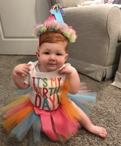Red head baby on 1st birthday sitting on the floor with a colorful tutu and party hat