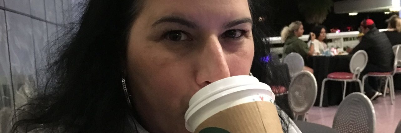 A photo of the writer wearing Mickey ears and drinking out of a Starbucks cup.