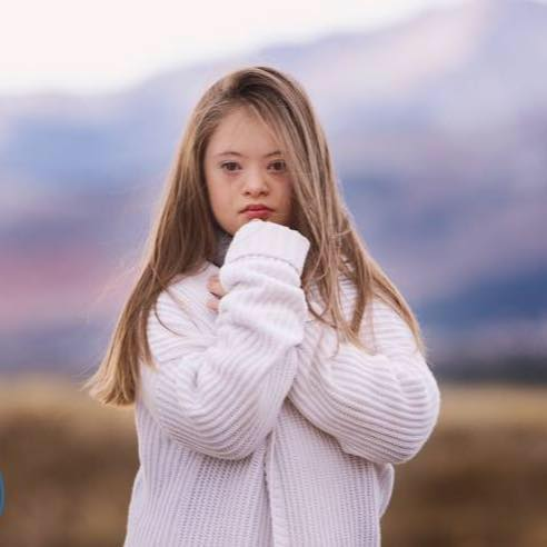Image of kennedy Garcia posing, she wear a white fluffy sweater and she is resting her chin on her fist. Outdoor shot.