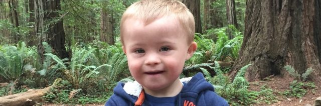 Little boy with Down syndrome, woods in background, he is smiling, holding his hads together and wearing a blue sweatshirt.
