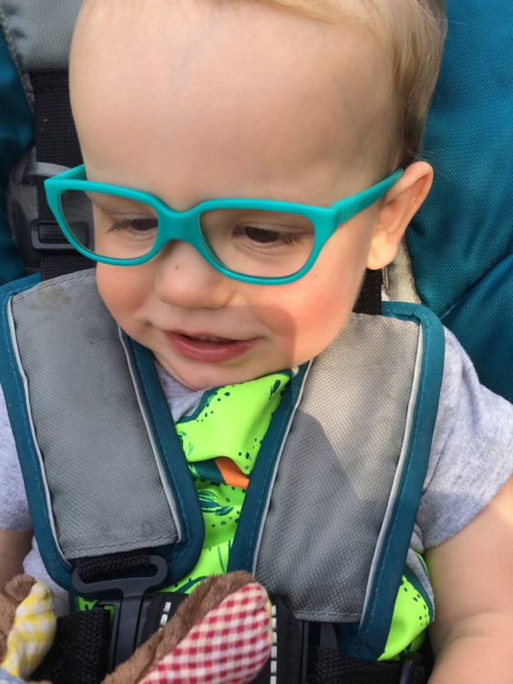 Lauren's son wearing glasses and smiling