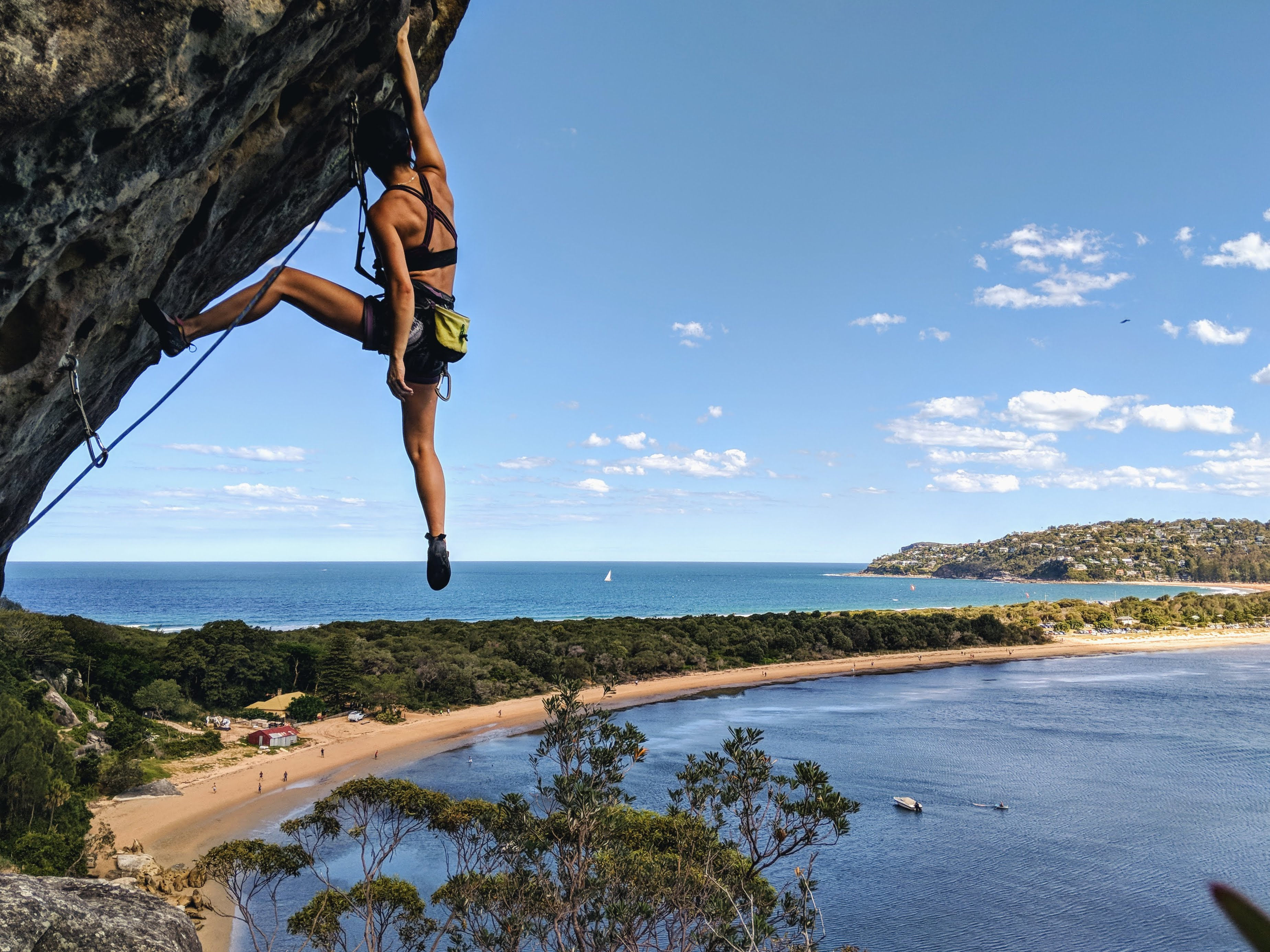 young woman rock climbing on cliffside hanging on by one hand tropical location