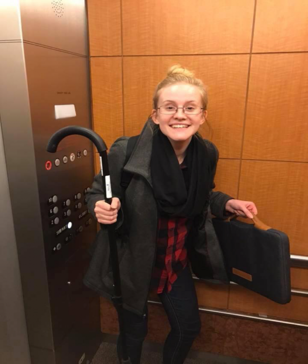 Melany holding an umbrella and standing in an elevator