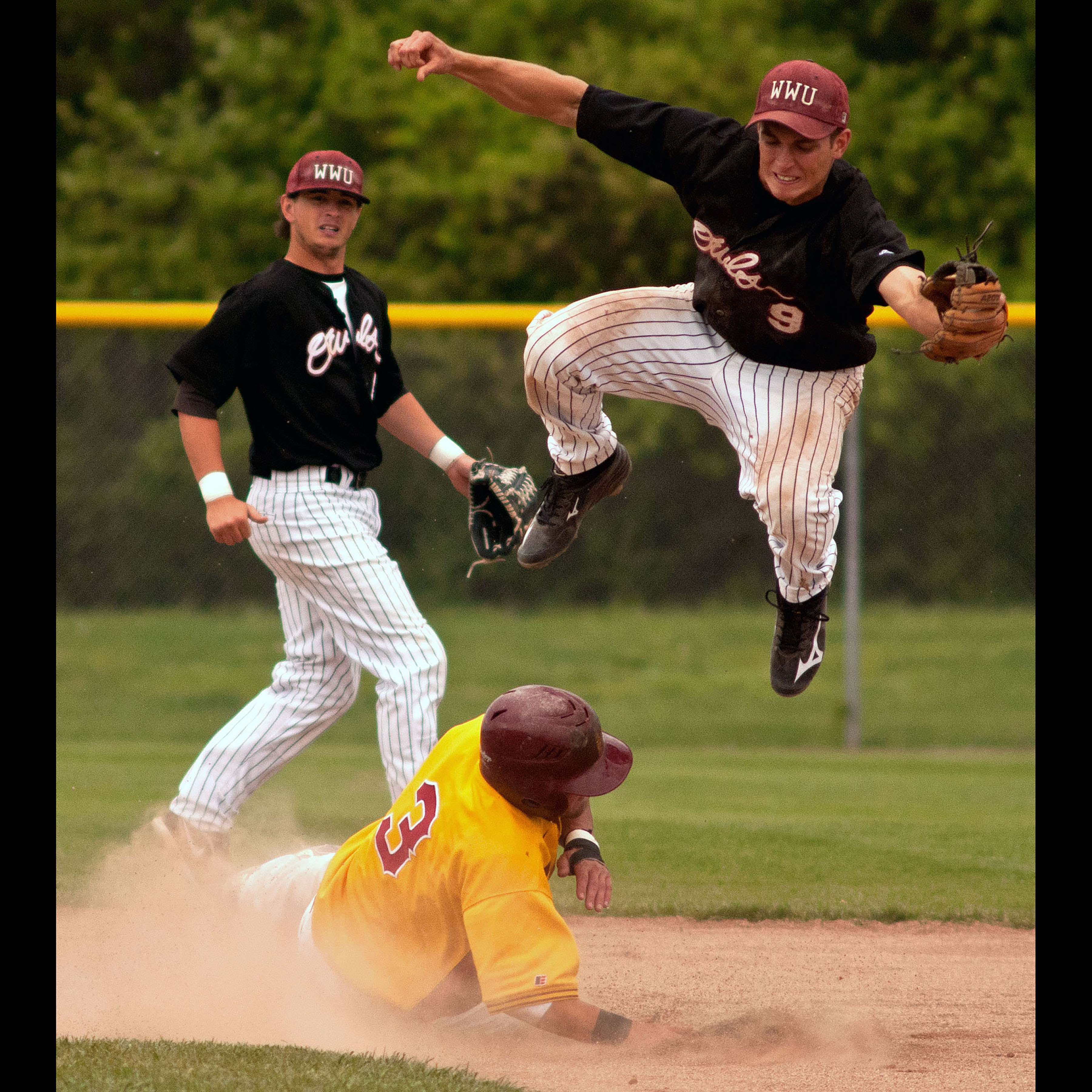 A photo of a baseball player in the air trying to catch a ball, while a player from another team slides into base.