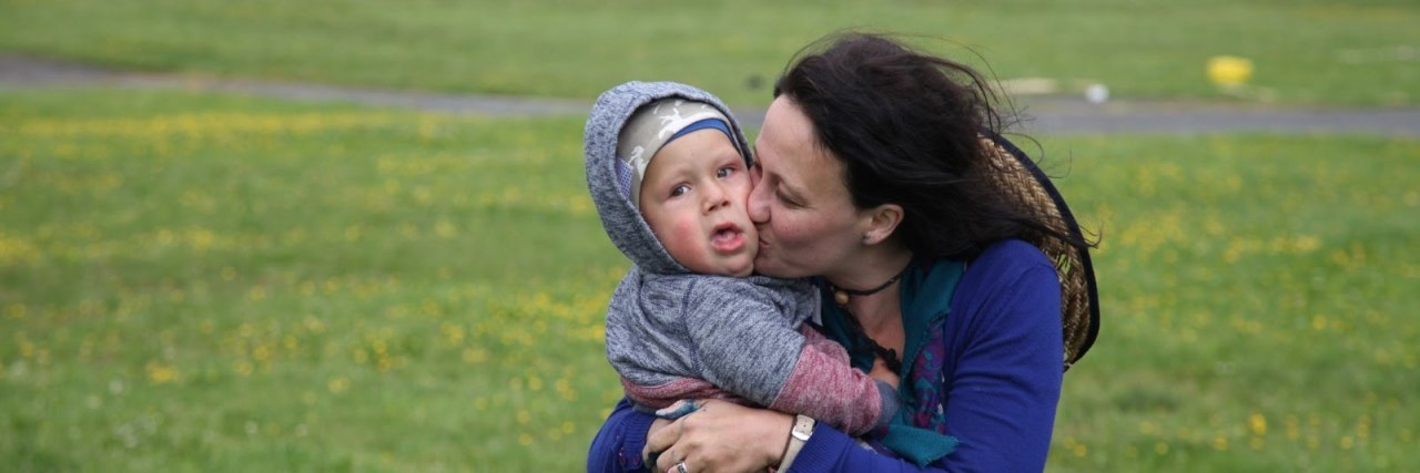 Mother kissingson outdoors. Boy is wearing a hooded sweatshirt and the hood is over his head. He seems to be around 2 years old.