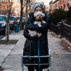 stacy london on street with walker holding small dog