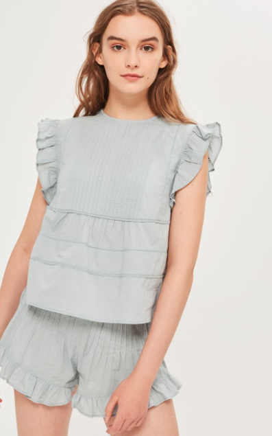light blue top with flutter sleeves and ruffled shorts