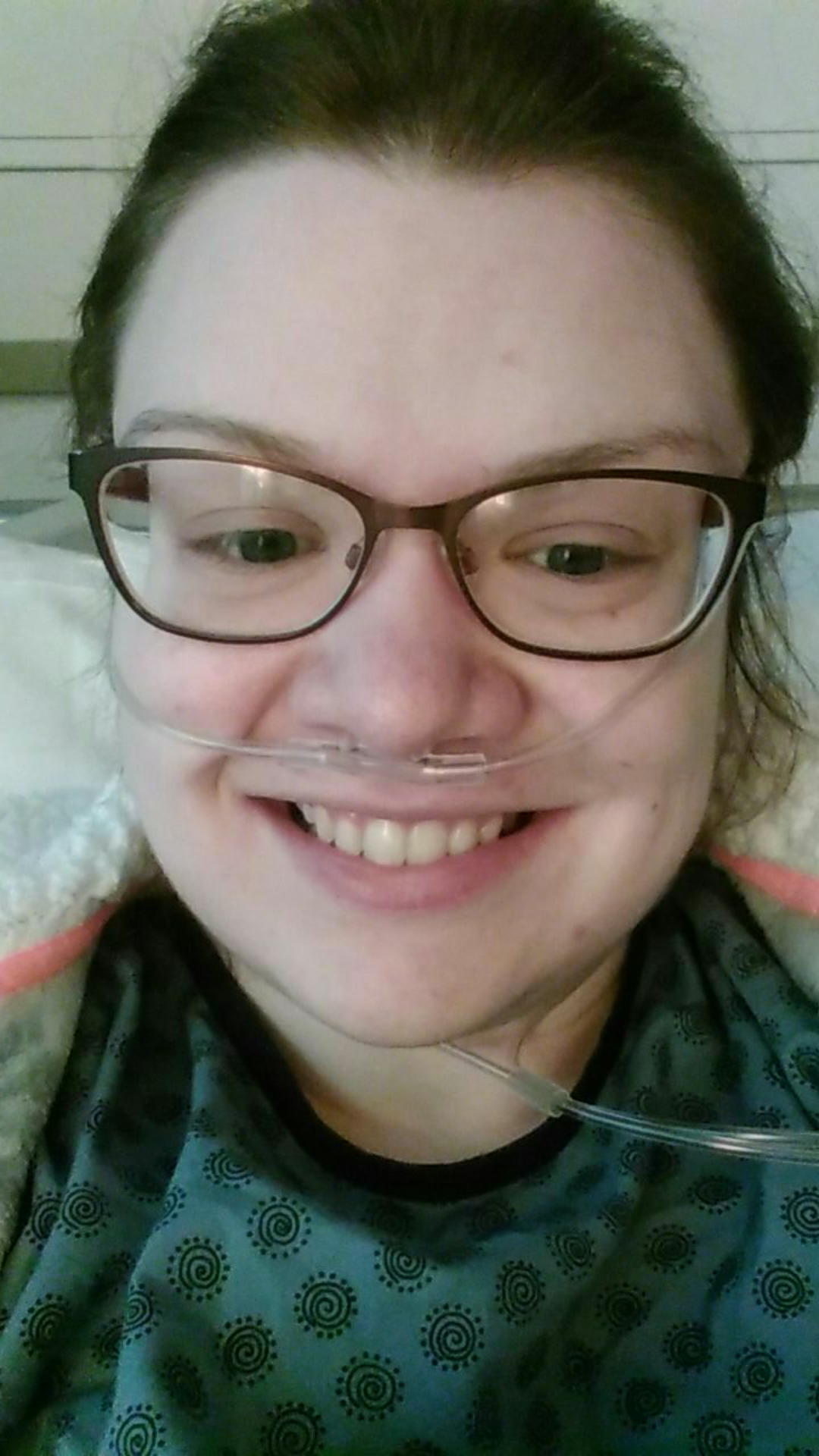 woman in the hospital wearing glasses and an oxygen tube in her nose