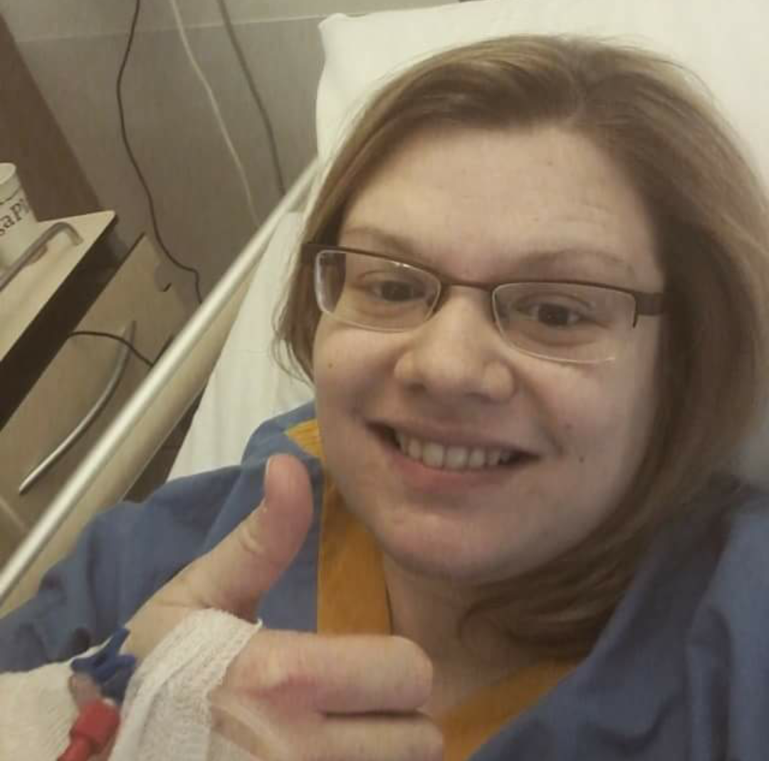 woman lying in a hospital bed and giving a thumbs up