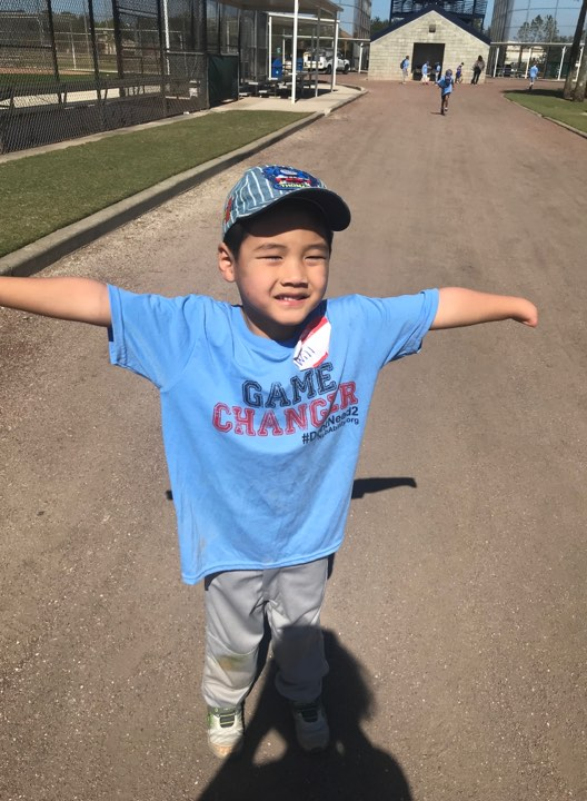 "Will Hawkins at baseball field, he is wearing a blue shirt that reads ""Game Changer"" and has his arms spread apart."