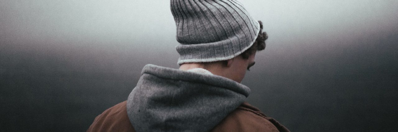 teen looking away from camera wearing hat against grey background