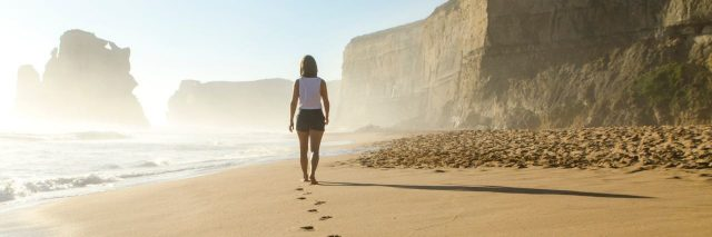 woman walking along a beach with a trail of footprints in the sand behind her