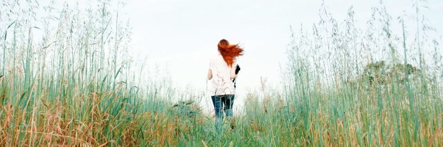 redhead woman running through long grass in field away from camera