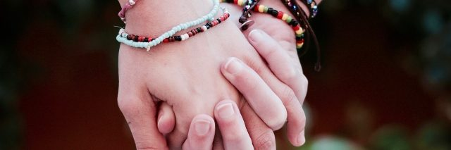 two women wearing bracelets and holding hands
